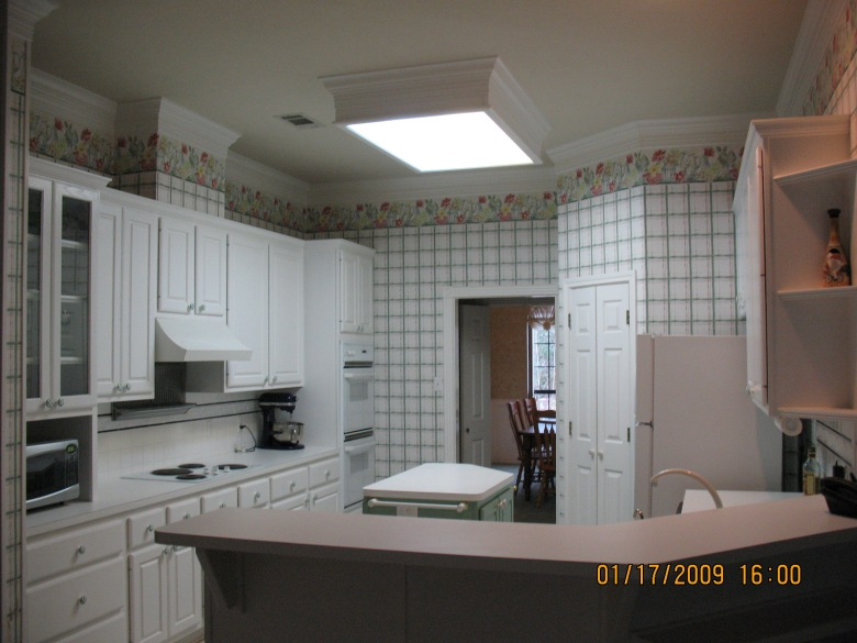 white kitchen with green gingham wallpaper, crappy countertops, and lots of green gigham accents