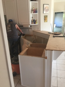 The sink area sans countertops. Back of a gentleman working on a countertop removal.